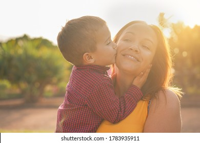 Young mother laughing and  carries her son in her arms - Child kiss his mother - Mother and child love