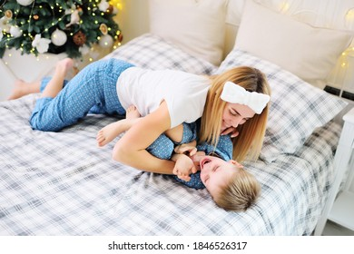 a young mother laughs and tickles her young son in pajamas while lying on the bed against the background of a Christmas tree. Christmas celebration.