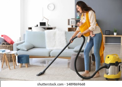 Young mother with little baby doing chores at home