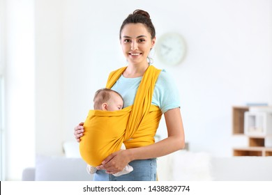 Young mother with little baby in sling at home