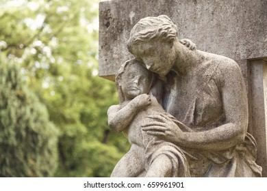 Young mother with little child monument on a tomb at a graveyard.