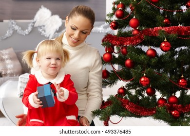Young mother and little daughter at christmas eve opening presents.