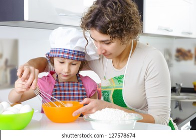 Young mother with little daughter cooking cookies