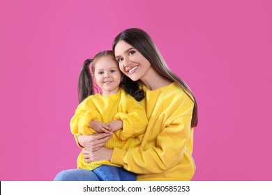 Young mother and little daughter on pink background