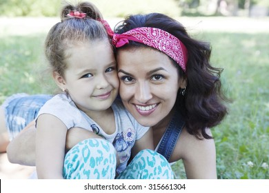 Young mother and little daughter on nature