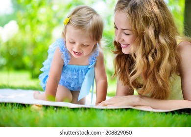 Young mother with little daughter reading book on green grass