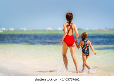 Young mother and little daughter running on the beach in Dominican Republic