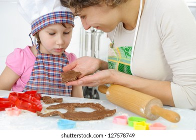 Young mother with little daughter shaping dough for cookies