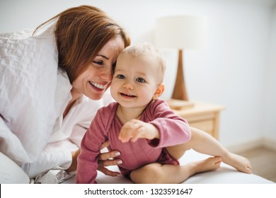 A young mother with little daughter sitting indoors on bed in the morning, playing.