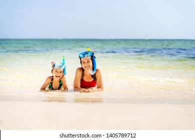 Young mother and little daughter in snorkeling masks enjoing the beach in Dominican Republic