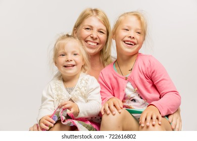 Young mother with little daughters, blondes, hug and laugh, happ