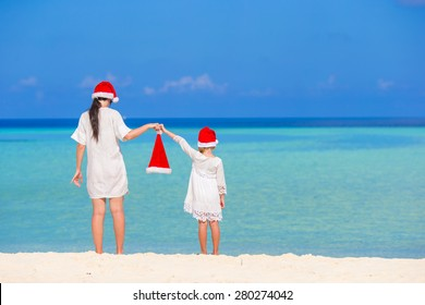 Young mother and little girl in Santa hat