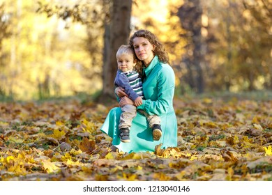 Young mother with little kid sitting on autumn leaves