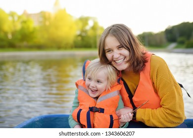 Young mother and little son boating on a river or pond at sunny summer day. Quality family time together on nature. Rest and traveling with kids.