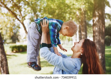 Young mother with little son having fun playing in the Park