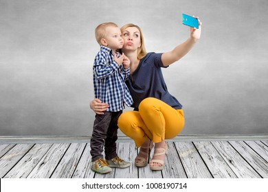 Young mother and little son are photographed on a mobile phone making selfie.Family leisure,entertainment and fun.