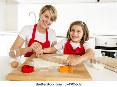 young mother and little sweet daughter in cook apron cooking together baking at modern home kitchen preparing desert with rolling pin rod smiling happy having fun