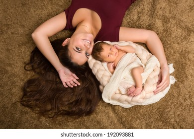 Young mother with long brown hair together with her baby
