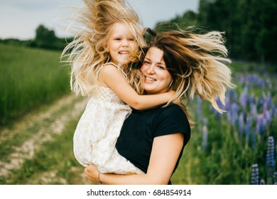 Young mother with long hair holding little daughter princess at hands. Playing with child. Pure, happy, kind, expressive emotional faces. Family at nature. Artistic kid. Laughing, smiling, embracing.