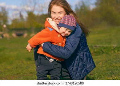 Young mother with long, well-groomed ginger hair wears blue warm jacket, young son in sweaters cap for year or two. girl hugs a child, squats, looks at the camera, a snow-white Hollywood smile