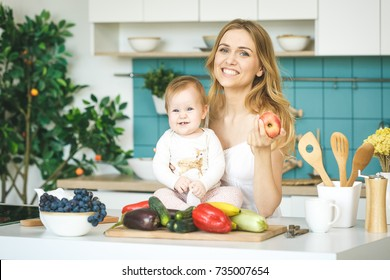 Young mother looking at camera and smiling, cooking and playing with her baby daughter in a modern kitchen setting. Healthy food concept.