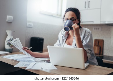 Young mother looking at the home budget. Young wife working at home.