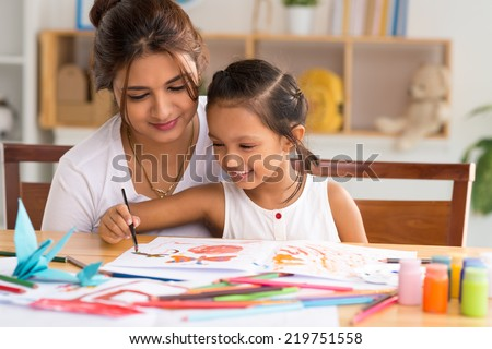 Young mother looking how her daughter drawing a picture
