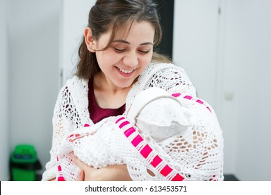 Young mother looking at newborn daughter in the hall of the perinatal center