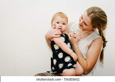 Young mother looks at two little teeth in a baby. The little girl with first teeth on the white background in the room. Close up. Infant. emotions happy of amazement.