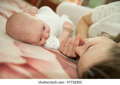 Young mother is lying with her little baby daughter