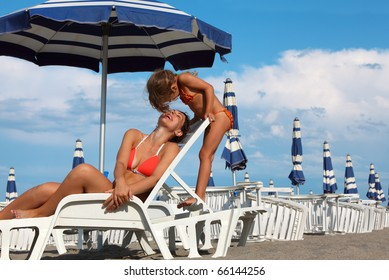 young mother lying on lounger under beach umbrella. little daughter in bathing suit standing near mother, rows of white loungers and blue umbrellas