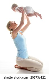 Junge Mutter macht mit ihrer 6 Monate alten Tochter postnatale Übungen einzeln auf weißem Hintergrund. Sie kniet auf dem Boden und hebt das Baby auf und lacht.