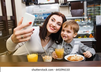 A young mother makes selfie with her little cute son at a table in a cafe