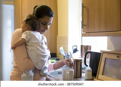 Young mother making a cup of tea with her baby son on her shoulder