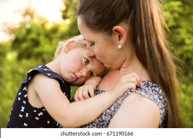 Young mother in nature holding little daughter in the arms.