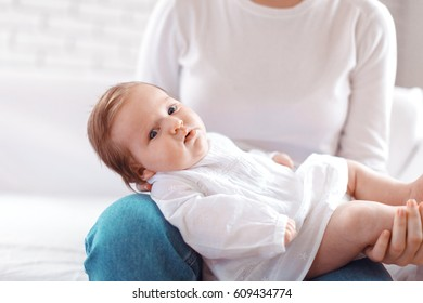 Young mother and newborn baby in white bedroom