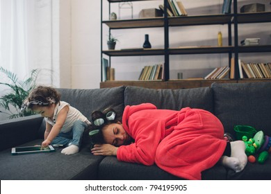 Young mother old is experiencing postnatal depression. Sad and tired woman with PPD. She does not want to play with her daughter