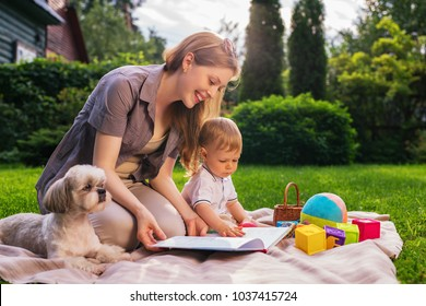Young mother with one year child and dog sitting in park and reading book