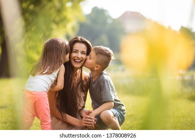 Young mother in park being kissed by children