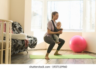 A young mother performs sports exercises squats and lunges with the child on the chest in the baby carrier. The joys and difficulties of motherhood. High quality photo