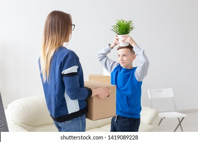 Young mother and a playful little son are holding a box with things and a flower in a pot standing in the living room in a new apartment. Housewarming and new housing concept.