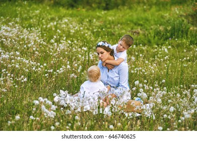 Young mother playing with children in nature. Concept of happy family