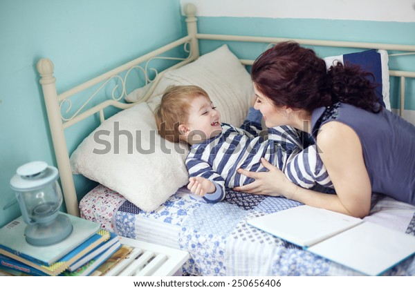 Young mother playing with her 2 years old little son at the bedroom