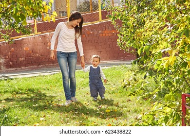 young mother playing with her baby. Mom and son walking in a park
