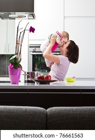 Young mother playing with her baby daughter in a modern kitchen setting.