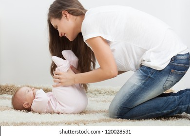 young mother playing with her daughter on carpet at home
