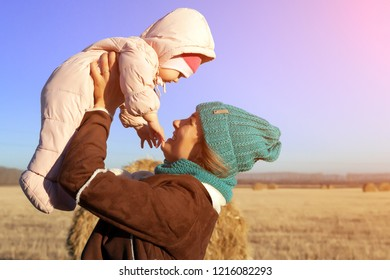 A young  mother playing her daughter and enjoying nature on the back of a background of autumn field landscape and haystick. The concept of livestyle and family outdoor recreation in autumn.