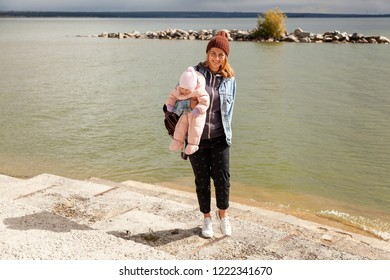 A young  mother playing her daughter and enjoying nature on the back of a background of autumn sea. The concept of livestyle and family outdoor recreation in autumn.