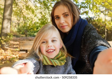 Young mother playing with her daughter in autumn park,  selfie photos, technology