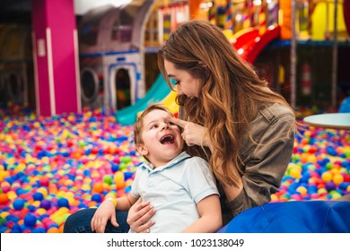 Young mother playing with her little son at the entertainment centre